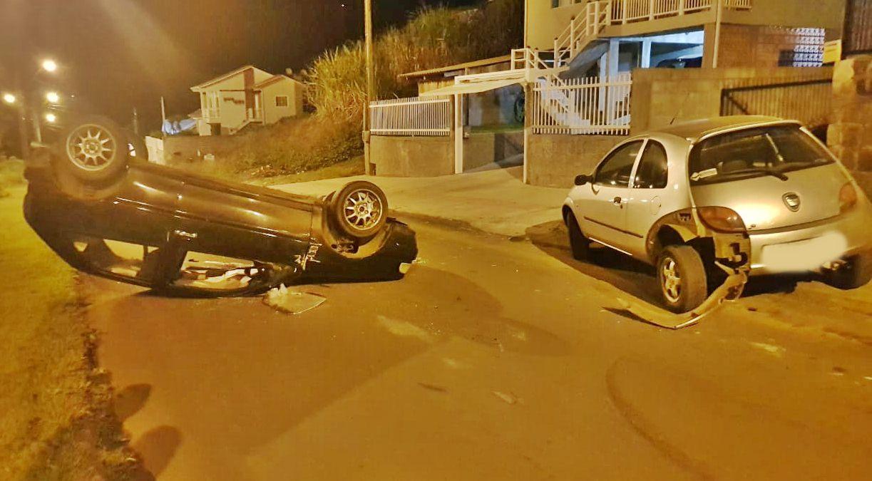 Condutor perde controle do carro, bate em outro que estava parado e capota